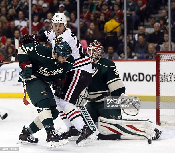 Bryan Bickell of the Chicago Blackhawks center is defended by Keith Ballard and goalie Ilya Bryzgalov of the Minnesota Wild in the first period of...