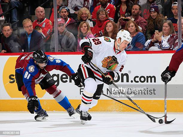 Bryan Bickell of the Chicago Blackhawks controls the puck against Tomas Vincour of the Colorado Avalanche at Pepsi Center on November 26 2014 in...