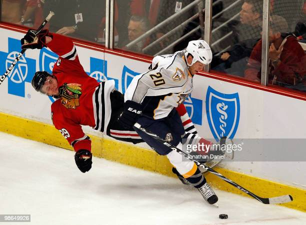 Bryan Bickell of the Chicago Blackhawks falls to the ice as battles for the puck with Ryan Suter of the Nashville Predators in Game Five of the...