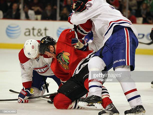 Bryan Bickell of the Chicago Blackhawks is held by Erik Cole of the Montreal Canadiens as he eyes the puck with Petteri Nokelainen at the United...