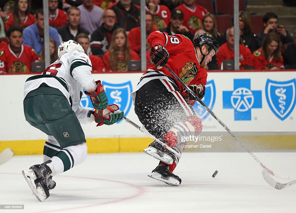 Bryan Bickell #29 of the Chicago Blackhawks is tripped by Erik Haula #56 of the Minnesota Wild in Game Two of the Second Round of the 2014 NHL Stanley Cup Playoffs at the United Center on May 4, 2014 in Chicago, Illinois.
