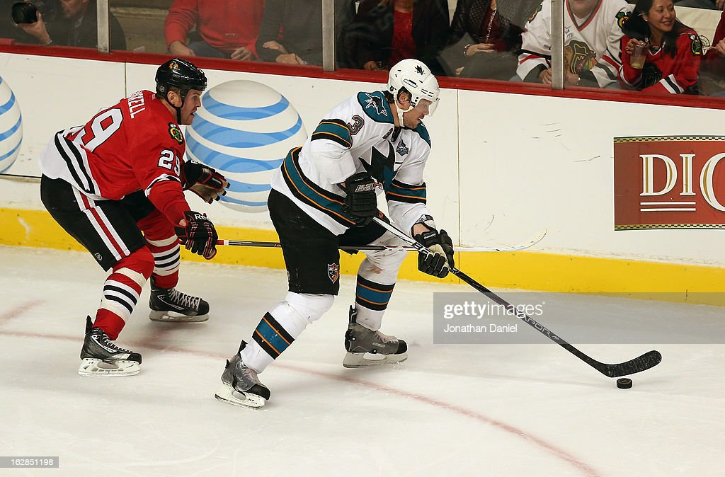 Bryan Bickell #29 of the Chicago Blackhawks jabs his stick between the legs of Douglas Murray #3 of the San Jose Sharks at the United Center on February 15, 2013 in Chicago, Illinois. The Blackhawks defeated the Sharks 4-1.