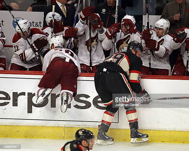 Bryan Bickell of the Chicago Blackhawks knocks Derek Morris of the Phoenix Coyotes over the wall and into the Coyote bench at the United Center on...