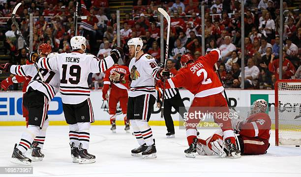 Bryan Bickell of the Chicago Blackhawks reacts to his third period goal with Jonathan Toews and Marian Hossa in front of Jimmy Howard and Brendan...