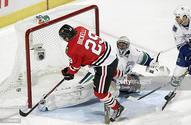 Bryan Bickell of the Chicago Blackhawks scores on Vancouver Canucks' goalie Roberto Luongo as Kevin Bieksa of the Canucks watches from the side in...