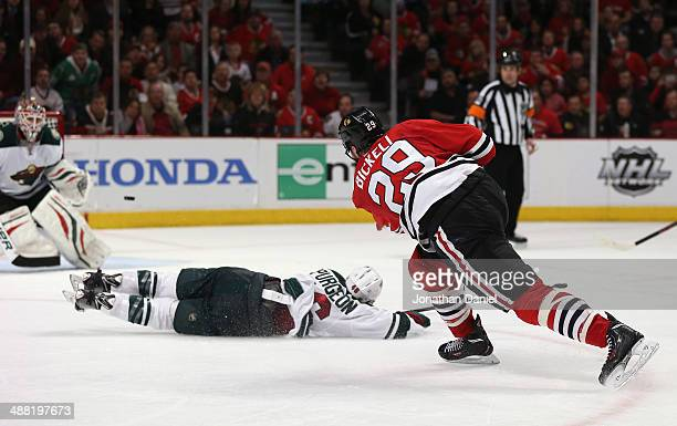 Bryan Bickell of the Chicago Blackhawks shoots the puck over Jared Spurgeon of the Minnesota Wild to score a third period goal against Ilya Bryzgalov...