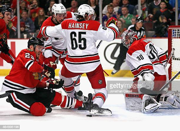 Bryan Bickell of the Chicago Blackhawks slips while trying to get off a shot between Ron Hainsey and Justin Faulk of the Carolina Hurricanes at Cam...