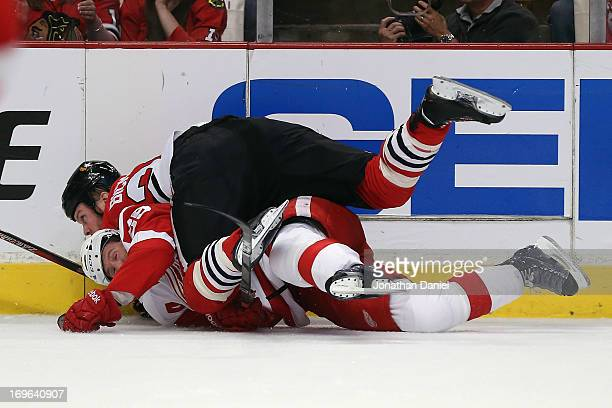 Bryan Bickell of the Chicago Blackhawks takes down Niklas Kronwall of the Detroit Red Wings in Game Seven of the Western Conference Semifinals during...