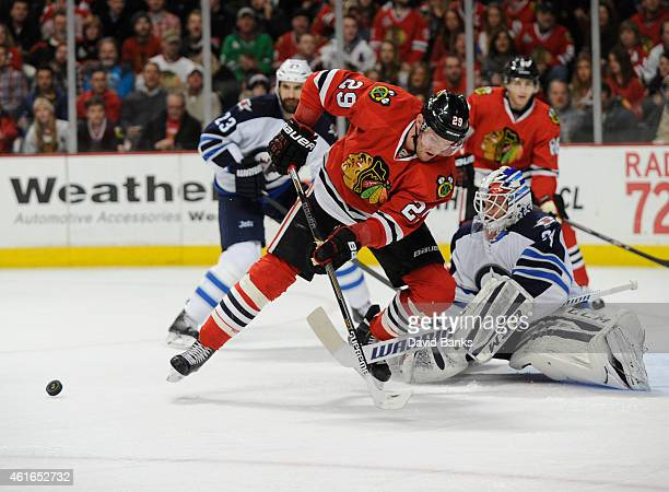 Bryan Bickell of the Chicago Blackhawks tries to control the puck in front of Michael Hutchinson of the Winnipeg Jets during the second period on...