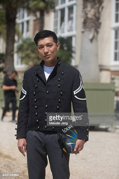 Bryan Boy wears a Ports 1961 military-style jacket, a Loewe clutch and Valentino trousers at the Sacai show at Orangerie du Jardin du Luxembourg on...