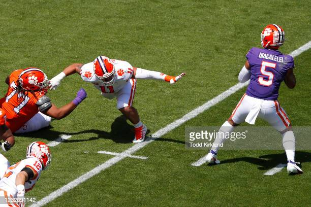 Bryan Bresee of the Clemson Tigers is held as he pressures D.J. Uiagalelei of the Orange Team during the Clemson Orange and White Spring Game at...