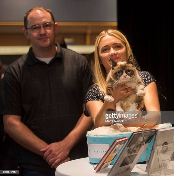 TORONTO ON AUGUST 9 Bryan Bundesen and Tabby Bundesen arrive with Grumpy Cat at Indigo in the Eaton Centre in Toronto August 9 2014