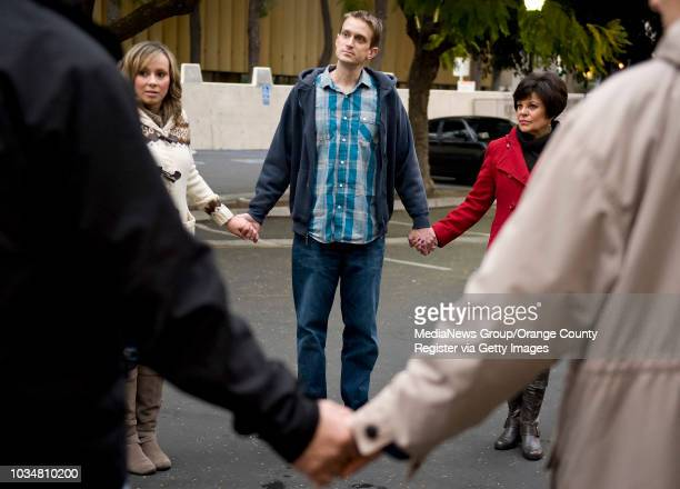 Bryan Crain center a volunteer with the Orange County Rescue Mission's Chili Van leads volunteers in prayer after serving homeless hot bowls of chili...