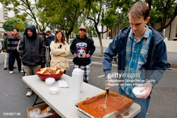 Bryan Crain right a volunteer with the Orange County Rescue Mission's Chili Van dishes out bowls of hot chili to the homeless in downtown Santa Ana...