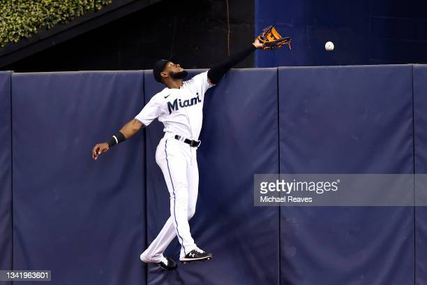 Bryan De La Cruz of the Miami Marlins can't reach a solo home run hit by Yadiel Hernandez of the Washington Nationals during the second inning at...