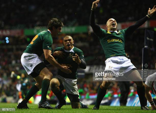 Bryan Habana of South Africa celebrates his try with team mate Conrad Jantjes and Jaque Fourie during the Investec Challenge match between England...