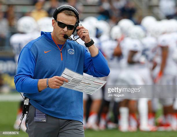 Bryan Harsin of the Boise State Broncos reviews his notes in the first half against the Connecticut Huskies at Rentschler Field on September 13 2014...