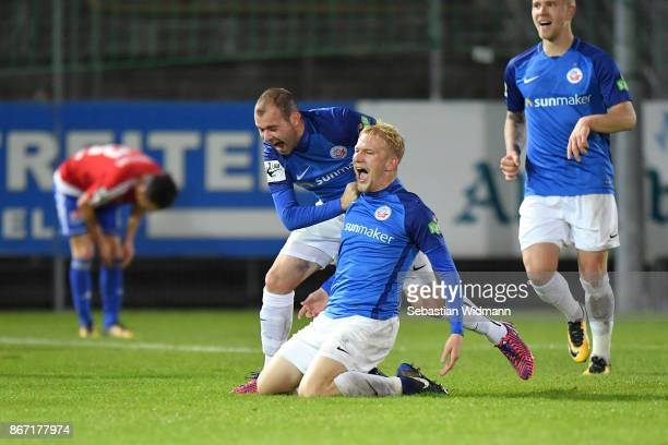 Bryan Henning of Hansa Rostock celebrates scoring his teams third goal with teammate Amaury Bischoffduring the 3. Liga match between SpVgg...