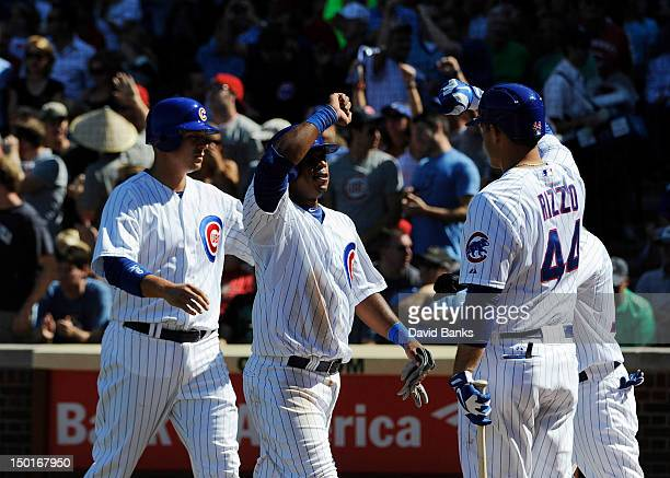 Bryan LaHair of the Chicago Cubs Luis Valbuena are greeted by Anthony Rizzo after scoring against the Cincinnati Reds on August 11 2012 at Wrigley...