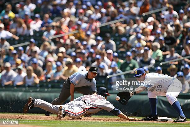 Bryan LaHair of the Seattle Mariners awaits the throw as Grady Sizemore of the Cleveland Indians dives back to first during the game on July 19, 2008...