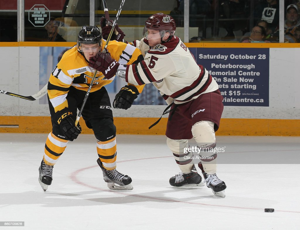 Bryan Laureigh #11 of the Kingston Frontenacs battles against Alex Black #5 of the Peterborough Petes in an OHL game at the Peterborough Memorial Centre on October 12, 2017 in Peterborough, Ontario.