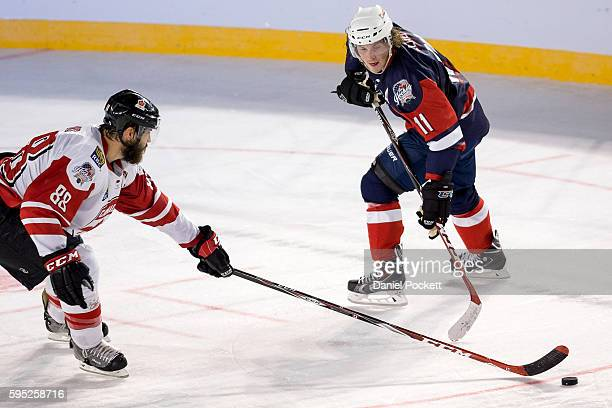Bryan Lerg of the United States of America and Brent Burns of Canada compete for the puck during the 2015 Ice Hockey Classic match between the United...