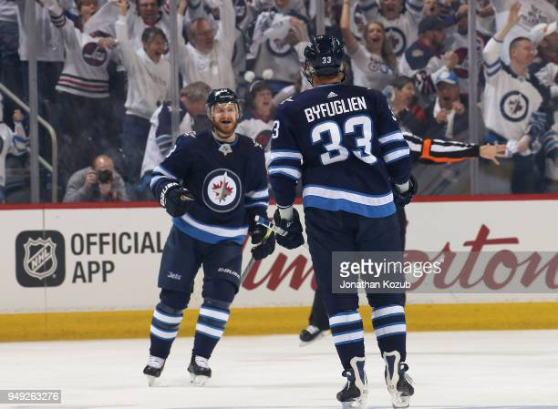 Bryan Little and Dustin Byfuglien of the Winnipeg Jets celebrate a first period goal against the Minnesota Wild in Game Five of the Western...