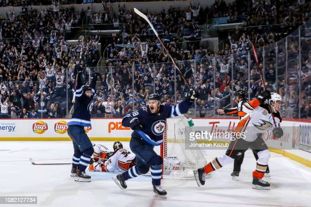 Bryan Little and Jacob Trouba of the Winnipeg Jets raise their arms in celebration after scoring the overtime winning goal against the Anaheim Ducks...