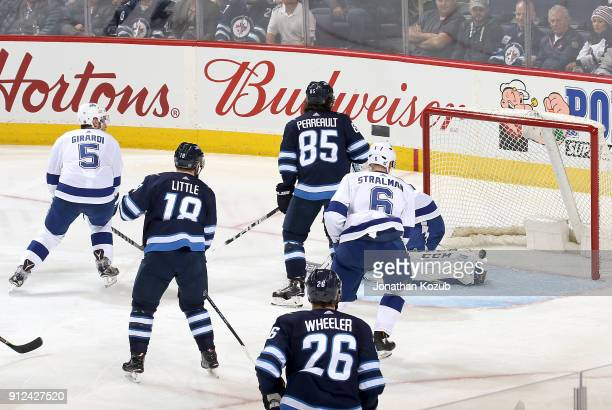 Bryan Little Mathieu Perreault and Blake Wheeler of the Winnipeg Jets watch as a shot by teammate Patrik Laine gets behind goaltender Louis Domingue...