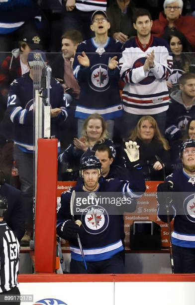 Bryan Little of the Winnipeg Jets acknowledges the fans as they celebrate his milestone becoming the franchise leader in games played during a first...