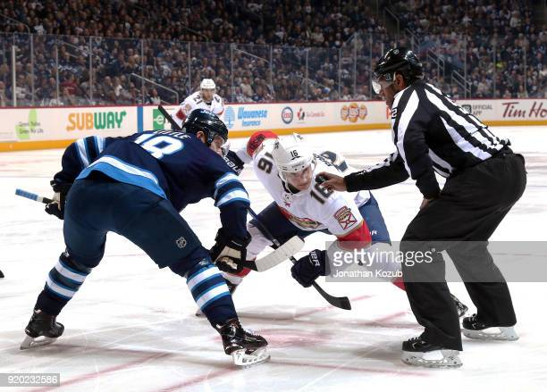 Bryan Little of the Winnipeg Jets and Aleksander Barkov of the Florida Panthers eye the puck as they get set for a first period faceoff at the Bell...
