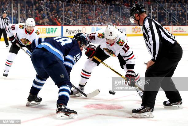 Bryan Little of the Winnipeg Jets and Artem Anisimov of the Chicago Blackhawks keep their eyes on the puck during a third period faceoff at the Bell...