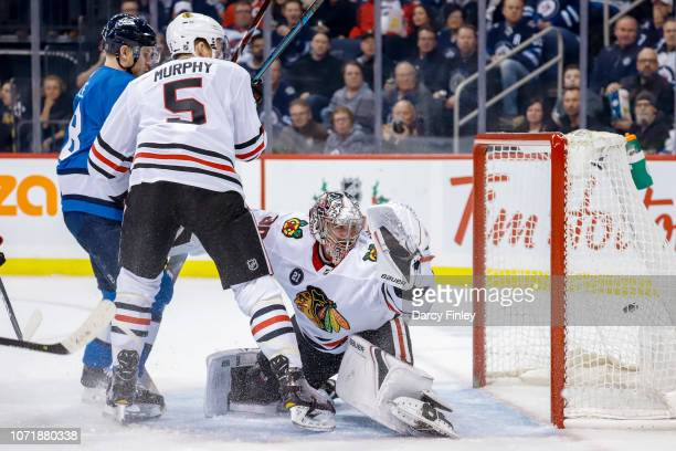 Bryan Little of the Winnipeg Jets and Connor Murphy of the Chicago Blackhawks watch as the puck gets behind goaltender Cam Ward on a shot by Kyle...