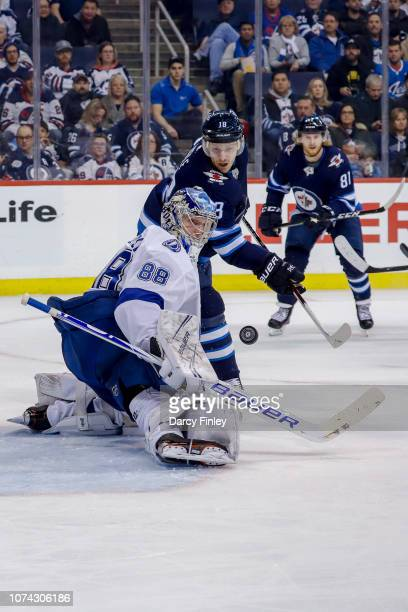 Bryan Little of the Winnipeg Jets and goaltender Andrei Vasilevskiy of the Tampa Bay Lightning keep an eye on the loose puck during second period...