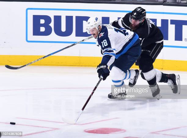 Bryan Little of the Winnipeg Jets and Jake Muzzin of the Los Angeles Kings battle for the puck at STAPLES Center on December 18 2018 in Los Angeles...