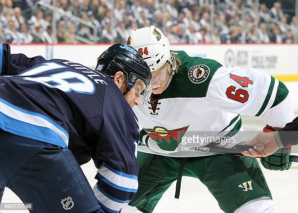 Bryan Little of the Winnipeg Jets and Mikael Granlund of the Minnesota Wild focus on the puck as they get set for a third period faceoff at the MTS...
