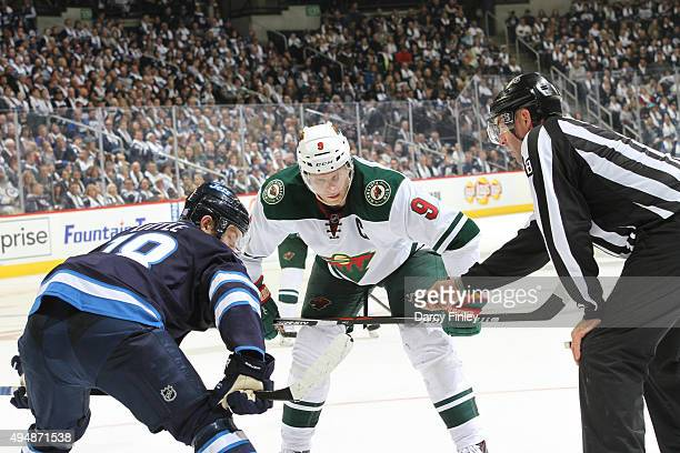 Bryan Little of the Winnipeg Jets and Mikko Koivu of the Minnesota Wild get set for a third period faceoff at the MTS Centre on October 25 2015 in...
