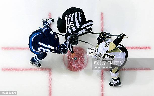 Bryan Little of the Winnipeg Jets and Sidney Crosby of the Pittsburgh Penguins take a third period faceoff at the MTS Centre on December 27 2015 in...