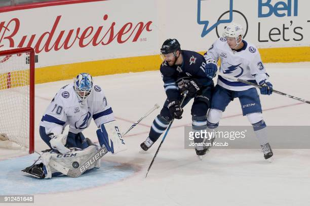 Bryan Little of the Winnipeg Jets and Yanni Gourde of the Tampa Bay Lightning look on as goaltender Louis Domingue makes a pad save during third...