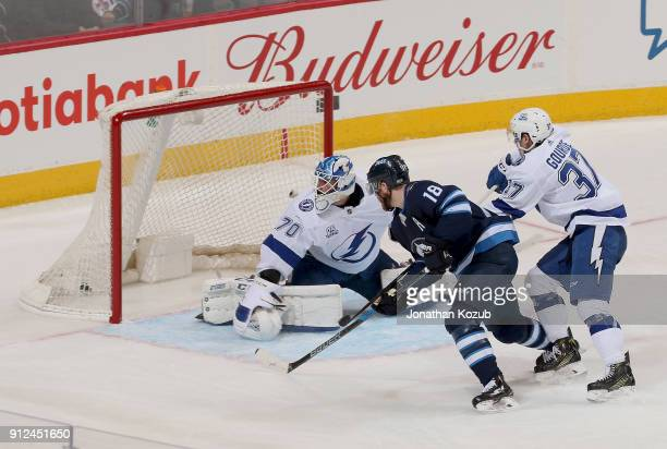 Bryan Little of the Winnipeg Jets and Yanni Gourde of the Tampa Bay Lightning watch as the puck gets behind goaltender Louis Domingue for a third...