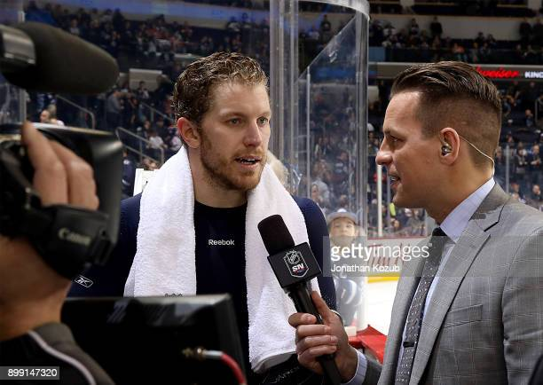 Bryan Little of the Winnipeg Jets answers questions from Sportsnet reporter Sean Reynolds during first intermission against the Edmonton Oilers at...