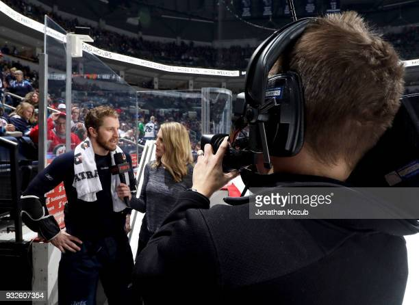 Bryan Little of the Winnipeg Jets answers questions in an interview with TSN reporter Sara Orlesky during the second intermission of NHL action...