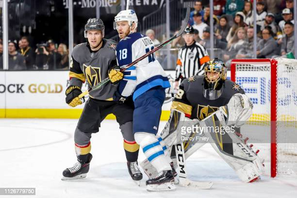 Bryan Little of the Winnipeg Jets battles for position against Shea Theodore and goaltender MarcAndre Fleury of the Vegas Golden Knights as they keep...
