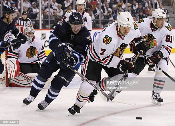 Bryan Little of the Winnipeg Jets battles for the puck with Brent Seabrook of the Chicago Blackhawks in second period action in an NHL game at the...