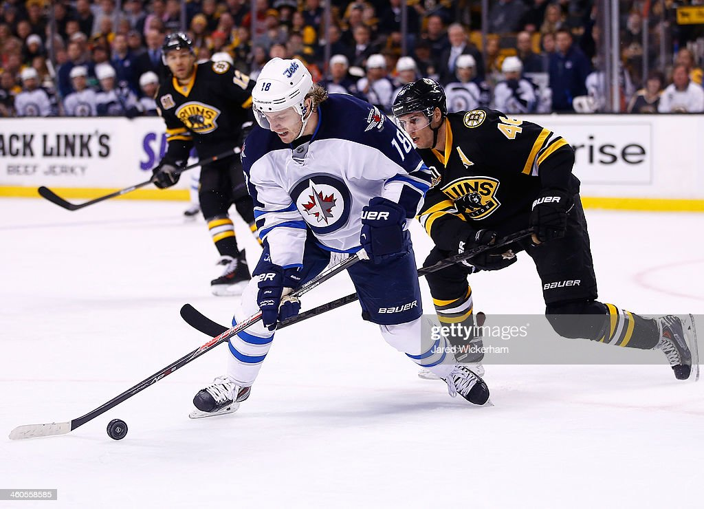 Bryan Little #18 of the Winnipeg Jets carries the puck in the offensive zone in front of David Krejci #46 of the Boston Bruins in the second period during the game at TD Garden on January 4, 2014 in Boston, Massachusetts.