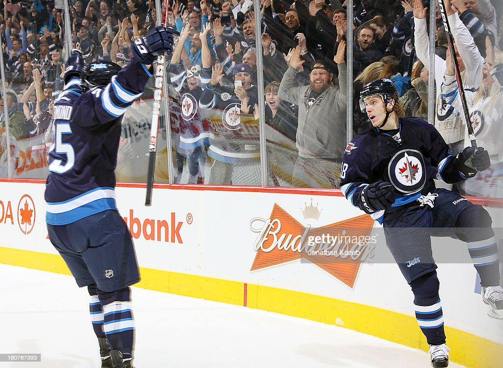 Bryan Little #18 of the Winnipeg Jets celebrates his overtime winner against the Florida Panthers as teammate Zach Redmond #25 joins him to celebrate in front of delirious fans at the MTS Centre on February 5, 2013 in Winnipeg, Manitoba, Canada.