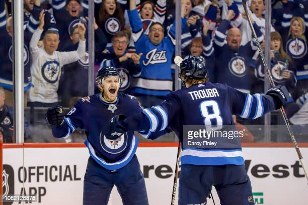 Bryan Little of the Winnipeg Jets celebrates with teammate Jacob Trouba after scoring the overtime winning goal against the Anaheim Ducks at the Bell...