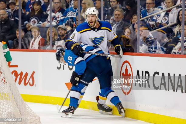 Bryan Little of the Winnipeg Jets checks Joel Edmundson of the St Louis Blues along the boards during first period action at the Bell MTS Place on...