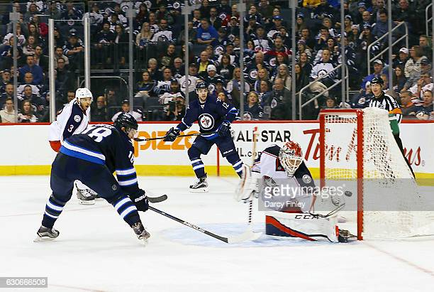 Bryan Little of the Winnipeg Jets deflects the puck past goaltender Sergei Bobrovsky of the Columbus Blue Jackets for a third period goal at the MTS...