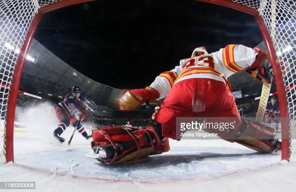 Bryan Little of the Winnipeg Jets fires the puck past David Rittich of the Calgary Flames to score an overtime goal during the 2019 Tim Hortons NHL...